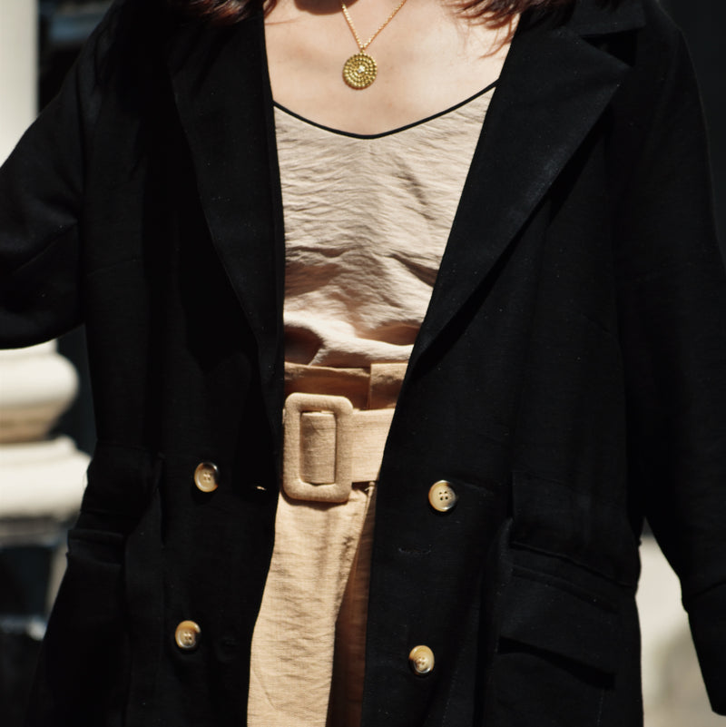 Woman wearing black blazer with four buttons open with shorts and cami top.