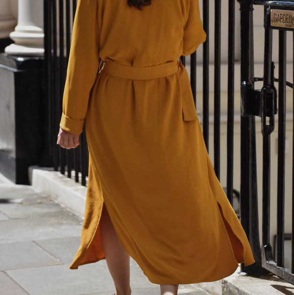 Back view of woman wearing Clemence waterfall trench coat in mustard gold outside.