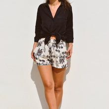 Woman wearing Ararose Rebecca floral shorts with navy linen shirt outside.
