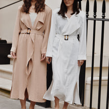 Two women wearing waterfall trench coats with belt at the waist. One coat is white, the other beige.