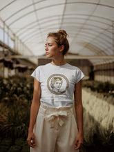 Blonde woman wearing Carnaby's Golden Goddess Organic T-shirt with gold Goddess Print with trousers.