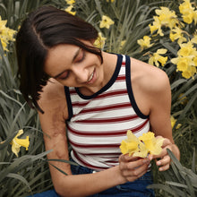 Woman wearing Ararose Isla striped red and white tank top with blue edging outside holding daffodils