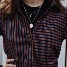 Close up of woman wearing striped navy and brown cotton flannel shirt tied at the waist.