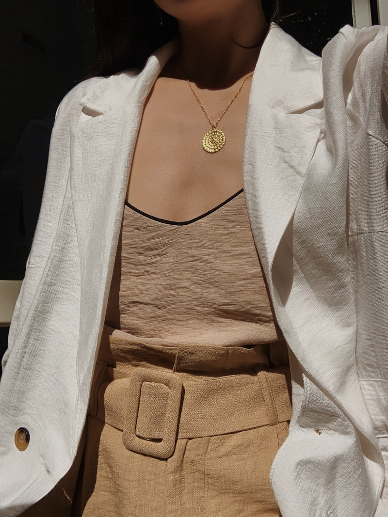 Woman wearing beige Estelle Cami top with black v neck edging and white blazer.