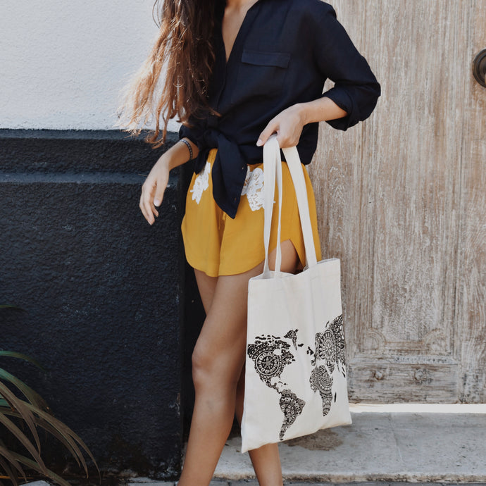 Woman wearing Isabel Mustard Lace Shorts with navy Melissa linen shirt and Kate world map bag.