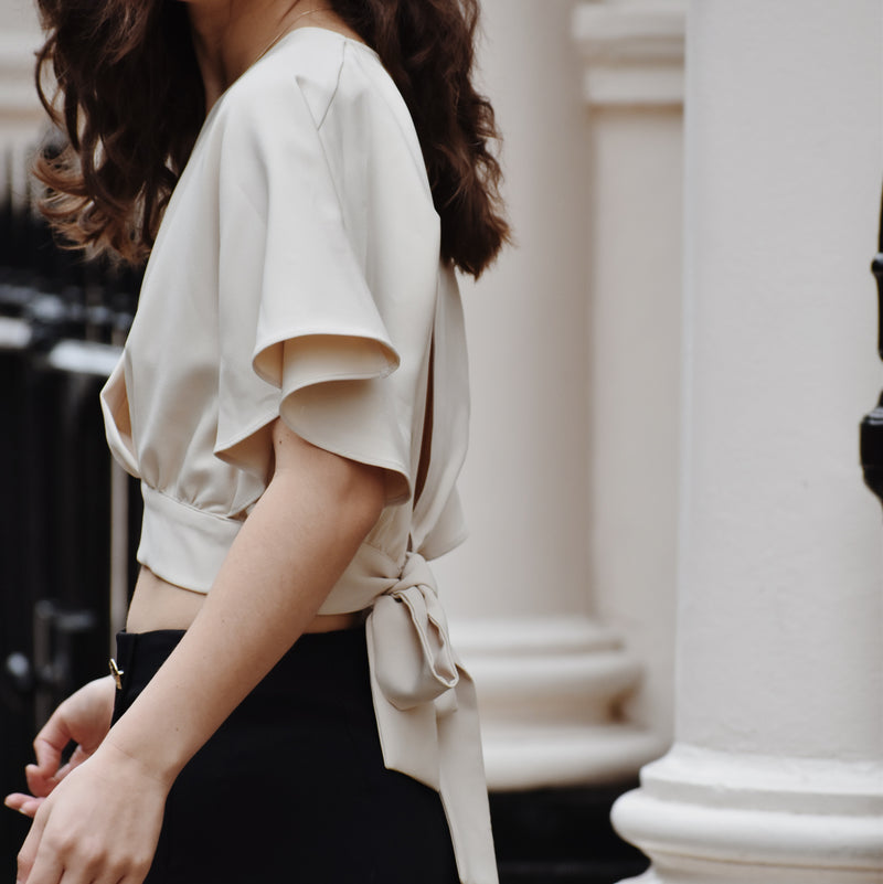 Woman wearing Chloé Beige Tie Top with black trousers and gold buttons.