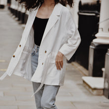 White blazer with pockets, button and waist tie.