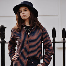 Woman wearing navy and brown striped cotton flannel shirt with jeans and a hat.