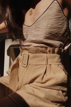 Woman wearing high waist long length beige shorts with cami top.