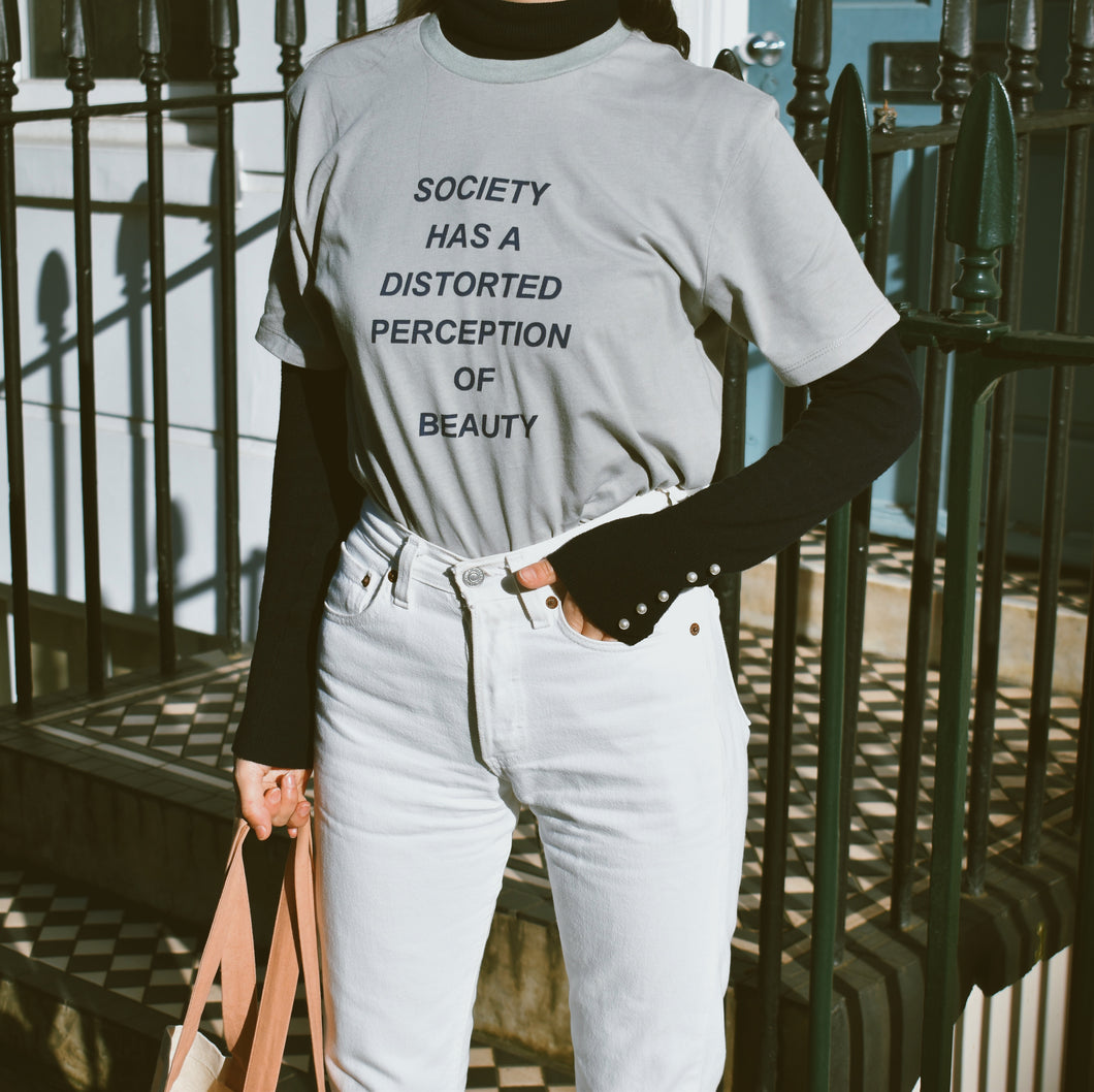 Woman wearing blue Ararose society t-shirt with black top and white jeans outside.