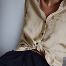 Woman wearing beige linen shirt tied at the waist with black shorts.