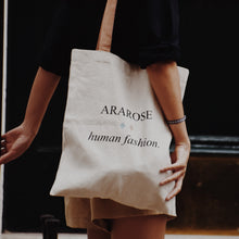 Woman wearing Ararose bag and navy linen shirt.