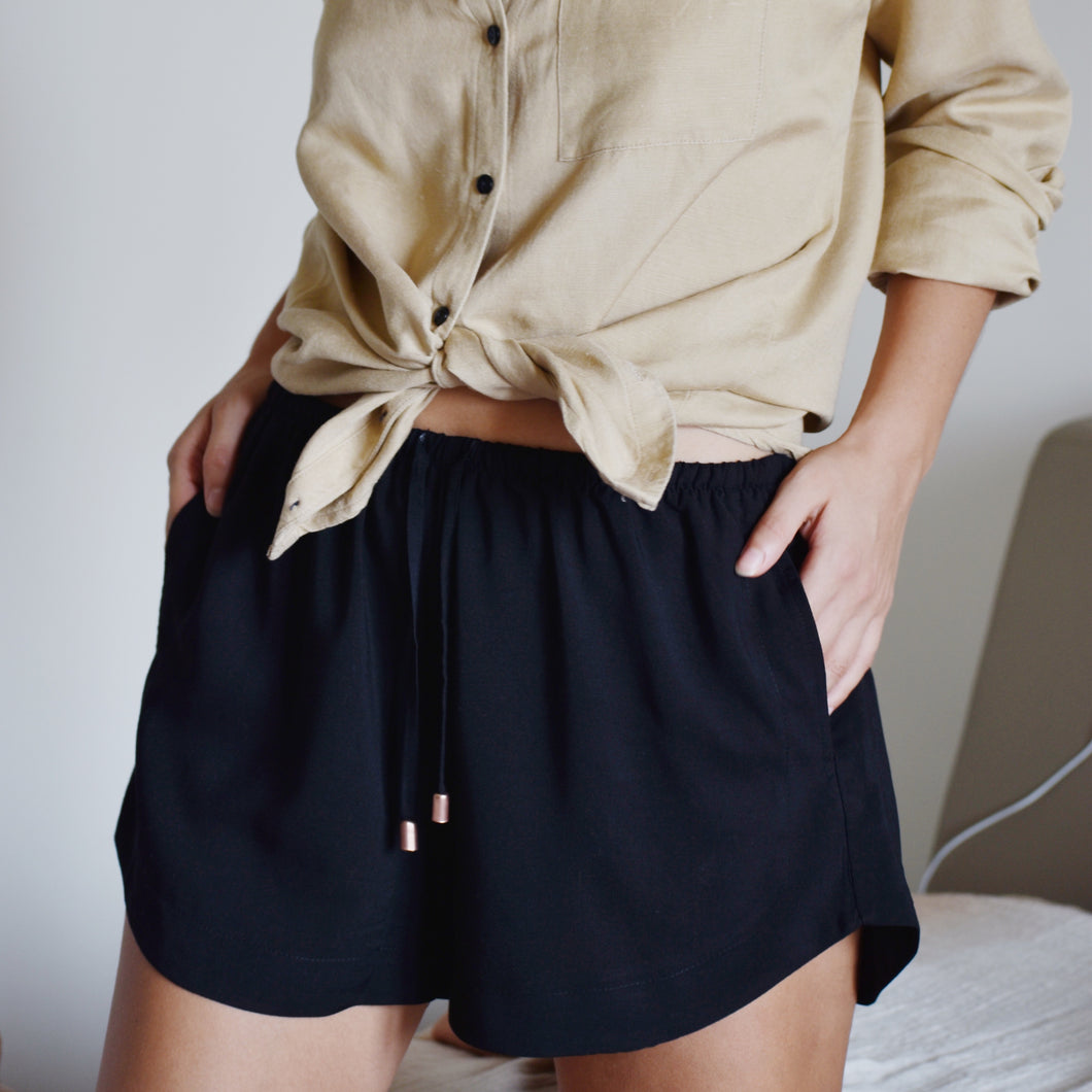 Woman wearing black shorts with pockets and ties with gold detail and beige linen shirt.