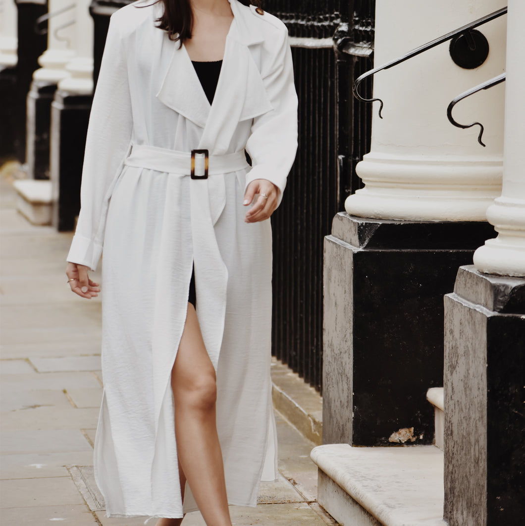 Woman wearing white waterfall trench coat with belt at the waist.