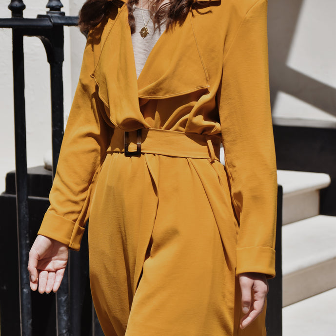 Woman wearing Clemence waterfall trench coat in mustard gold outside.