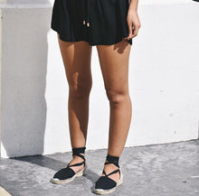 Woman wearing black jasmine shorts with espadrilles.