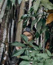 Woman in the jungle wearing headband.