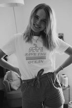 Blonde woman in white organic and recycled plastic bottle t-shirt with blue save the ocean print.