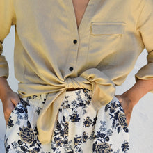 Woman wearing beige linen shirt tied at the waist with floral Rebeca shorts.