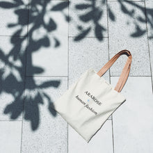 Flat lay of Ararose canvas bag on the floor with a tree shadow.