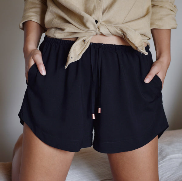 Woman wearing black jasmine shorts with beige linen shirt.