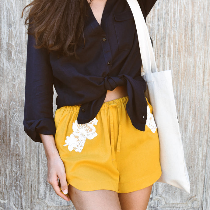 Woman wearing mustard gold Ararose Isabel shorts with white lace and navy Mellissa linen shirt.