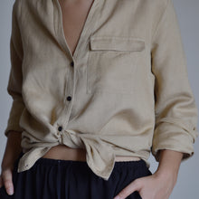 Woman wearing Lilian linen shirt tied at the waist with black shorts.