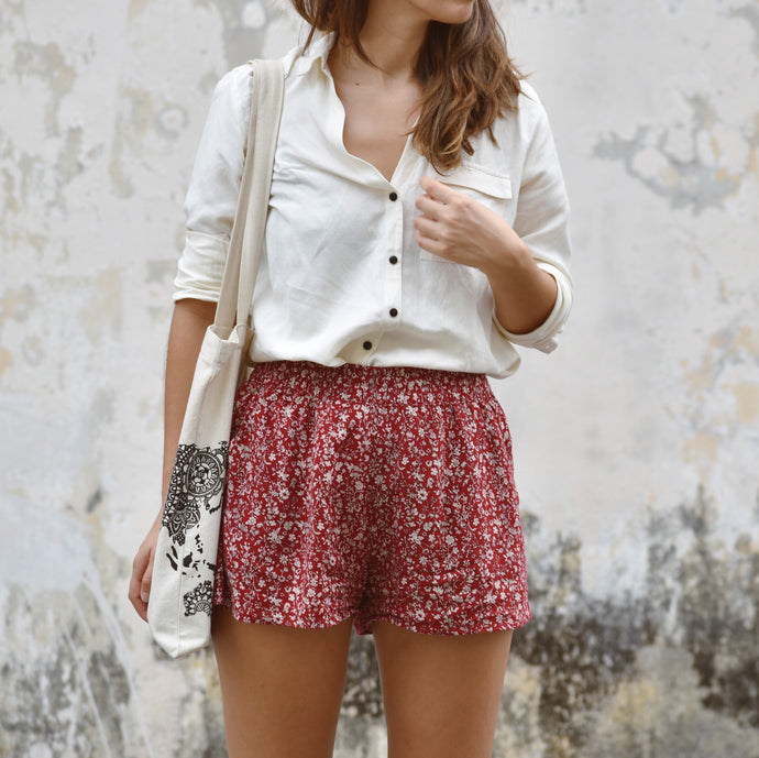 Woman wearing red Laura floral shorts with Bella linen shirt and Kate world map bag outside.