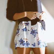Woman wearing Juliette white shorts with blue floral print and navy linen shirt.