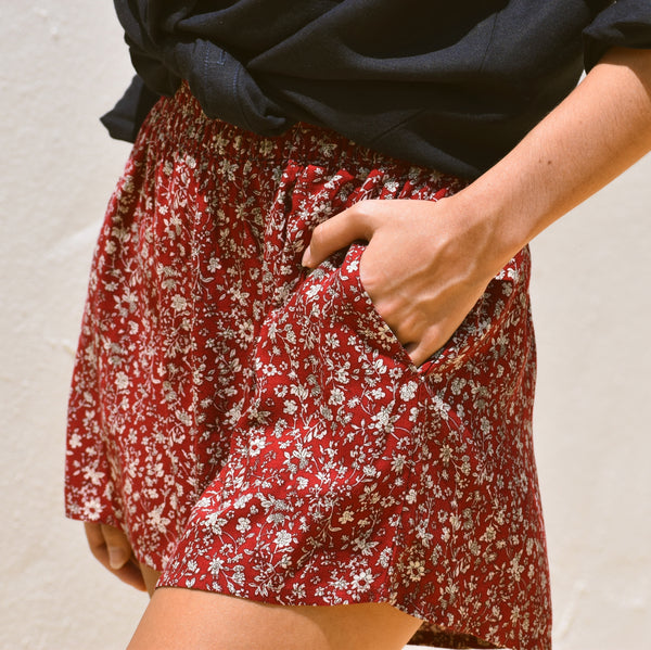 Woman wearing laura red floral shorts with navy linen shirt.