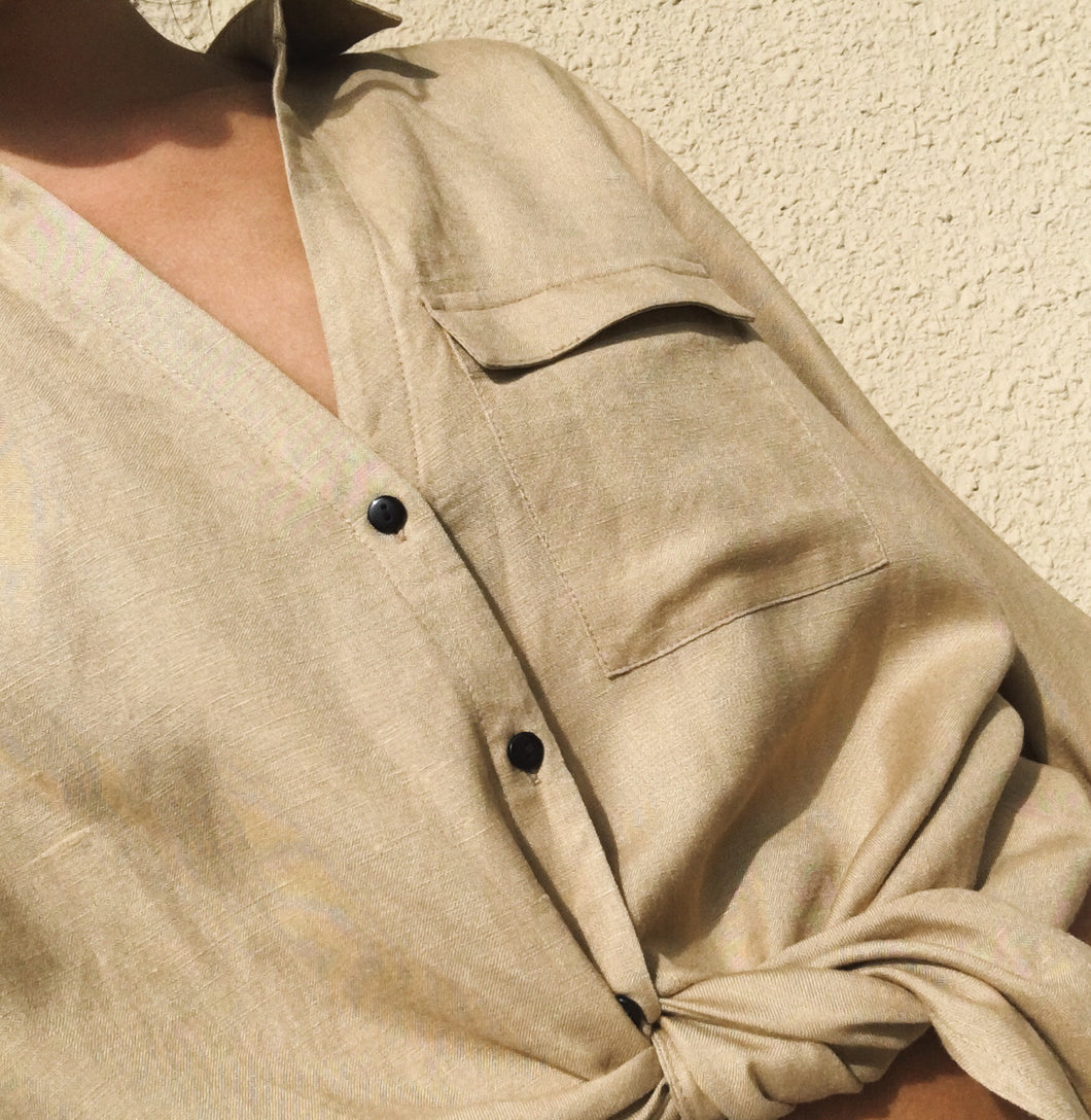 Woman wearing beige Ararose Lilian linen shirt tied at the waist with black buttons and pocket.