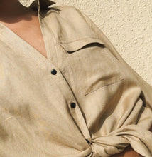 Woman wearing beige linen shirt tied at the waist.