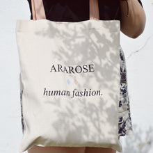 Woman holding Ararose bag with a plant shadow.