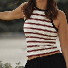 Woman wearing Ararose Isla striped red and white tank top with blue edging outside with black shorts