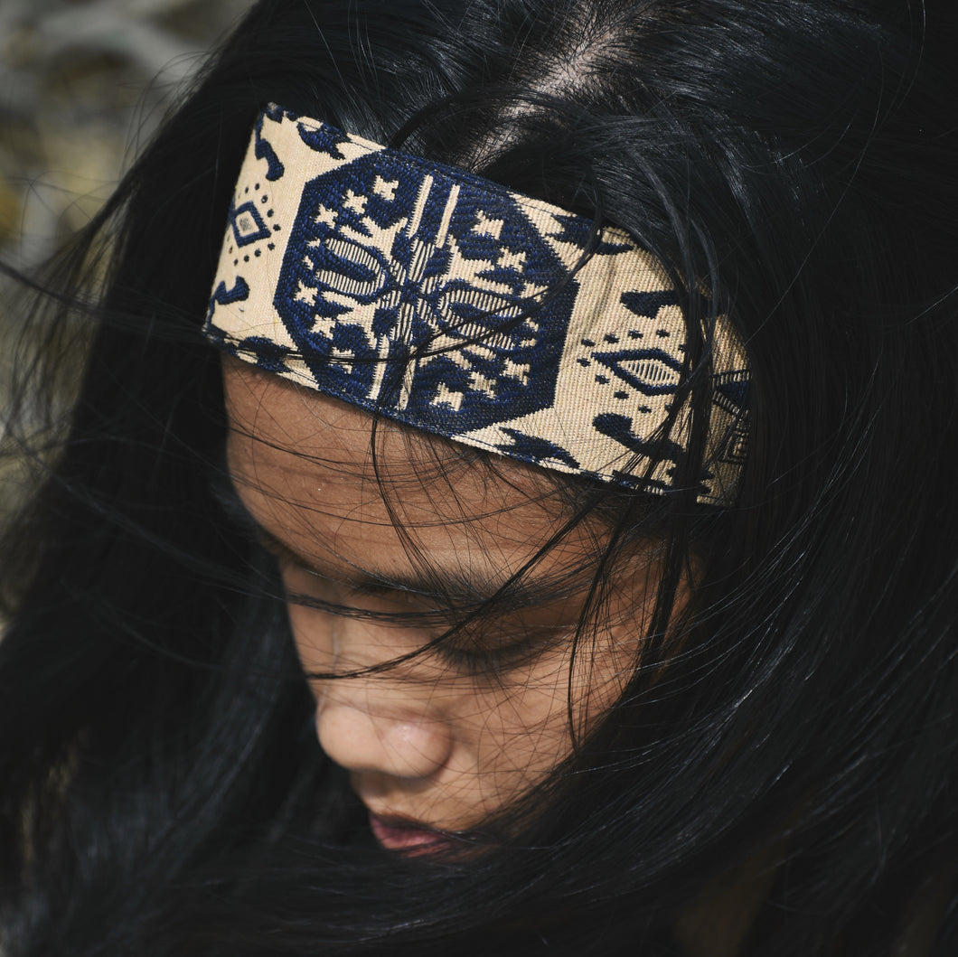 Woman with black hair wearing headband.