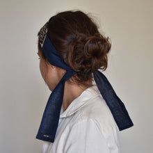 Back view of woman wearing Autumn headband with blue ties wearing Bella linen shirt.