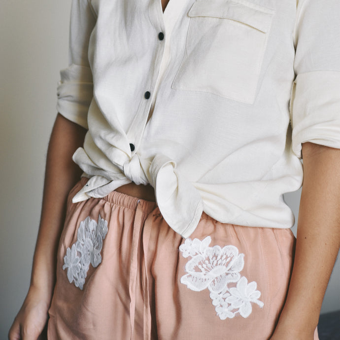 Woman wearing pink Olivia lace shorts with white lace pattern at the hip with white linen shirt.