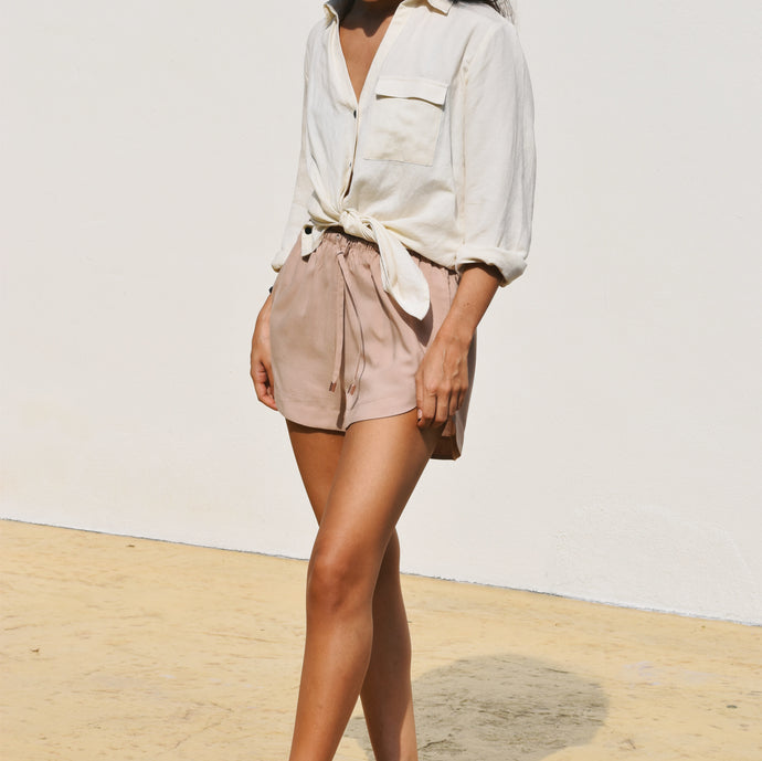 Woman wearing nude shorts with white linen shirt tied at the waist.