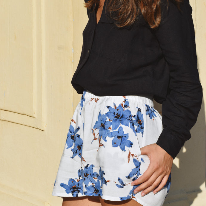 Woman wearing white shorts with blue floral print and navy linen shirt.