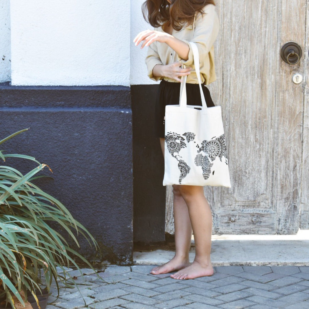 Woman wearing Kate's world map canvas bag outside.