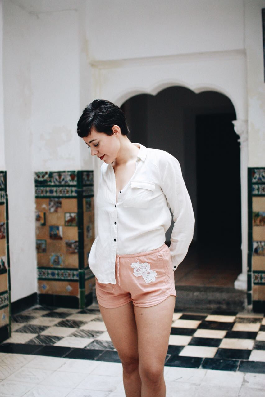 Woman wearing blush pink shorts with white lace patches at both hips.