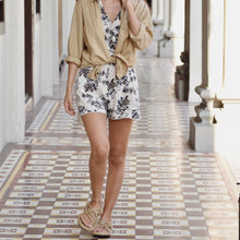 Woman wearing floral playsuit and beige Lilian shirt outside.