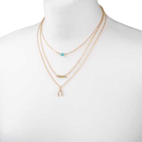 delicate gold layered necklace with turquoise bead and wishbone charm from our festival jewellery collection