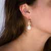 14kgold-small-spoked-hexagon-white-quartzite-earrings-on-model