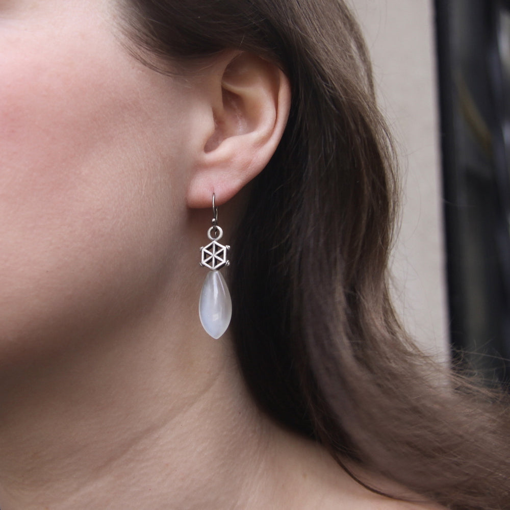 Load image into Gallery viewer, white-moonstone-silver-spoked-hexagon-earrings-model