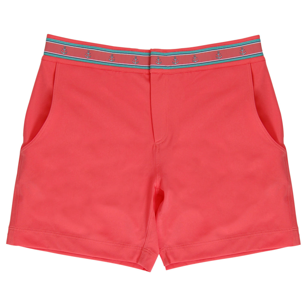 Neon coral swim trunk flat lay with anchor trim waistband