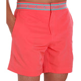 Neon coral swim trunk on model with hands in pockets