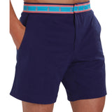 Navy blue swim trunk on model with hands in pockets