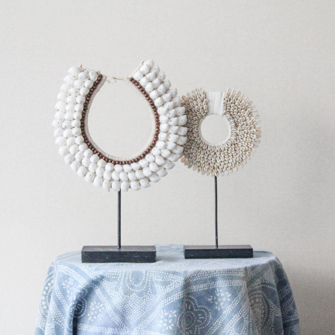 Handmade shell collar decor on a stand