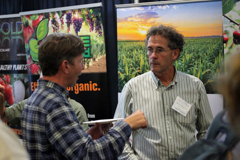 A Healthy Soil Summit attendee chats with a vendor at the Wednesday welcome mixer